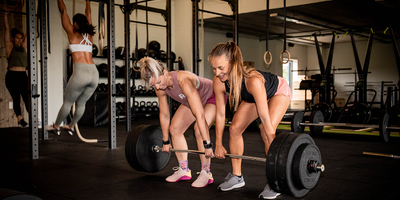Young_and_middle_age_women_performing_a_deadlift_with_pull_ups_in_the_background.jpg