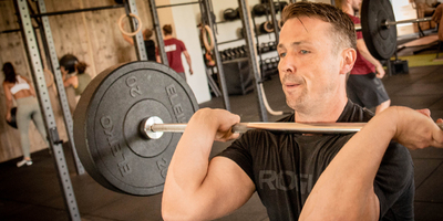 Strong_middle_aged_man_holding_barbell_in_front_rack.jpg
