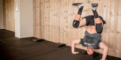 Fit_man_doing_kipping_hand_stand_push_ups_against_wooden_wall.jpg